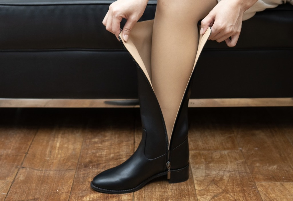 ロングブーツにつま先から足を入れて踵をしっかりと落とす